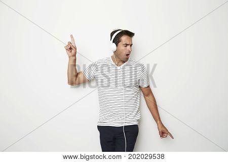 Dude loving to dance wearing headphones studio