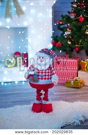 Dolls of Santa Claus and Christmas decorations with a white fireplace