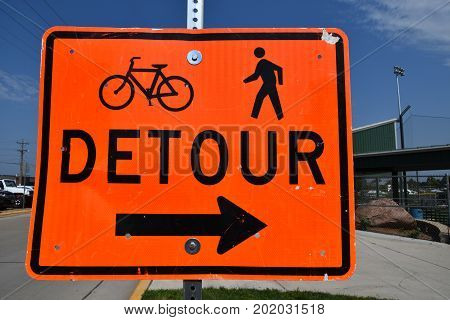 Signage on a road instructs bikers and pedestrians to turn right due to a detour.