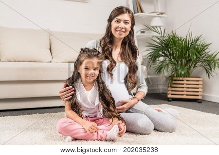 Pregnant Woman With Daughter Sitting On Rug
