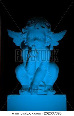 Sitting gypsum angel holding a birdie lit by blue light