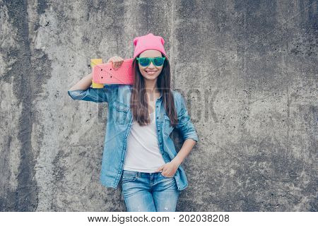 Be A Star! Young Attractive Hipster Girl With Skate Board On Concrete Wall`s Background, In Denim Ou