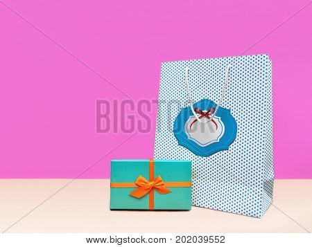 Gift box Trendy styled photo Stylish gift boxe and gift package are standing on a lilac wall background Front view Modern pop art photo with space for text