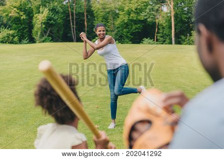 selective focus of african american woman throwing ball while playing baseball with family