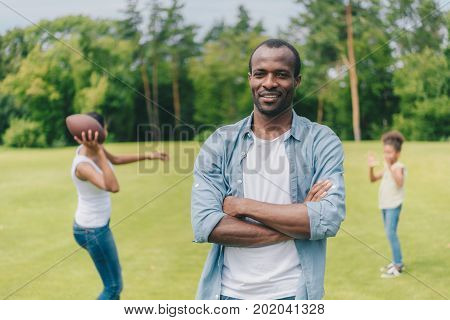 selective focus of smiling african american man looking at camera while family playing american football behind