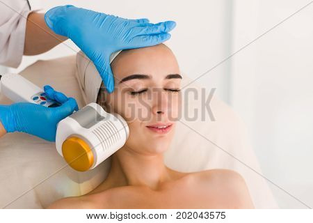 Skin care. Young woman receiving facial beauty treatment. Facial therapy. Anti-aging procedures. Woman with closed eyes.
