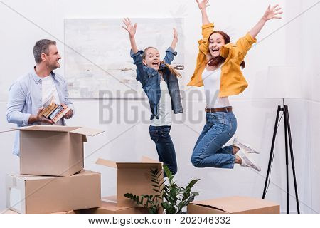 excited mother and teenage daughter jumping together while man unpacking boxes at new home