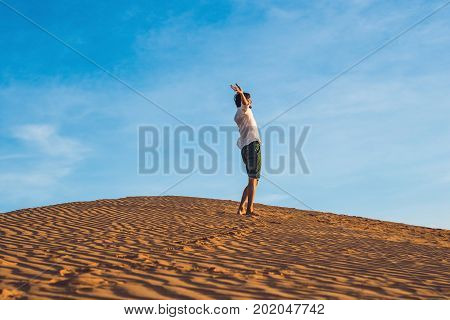 Beautiful Young Man Jumping Barefoot On Sand In Desert Enjoying Nature And The Sun. Fun, Joy And Fre