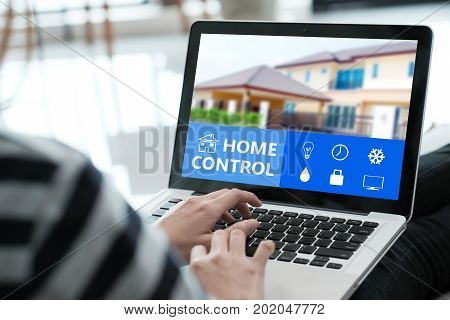Woman hand typing laptop computer with smart home control application on screen technology and lifestyle concept internet of things