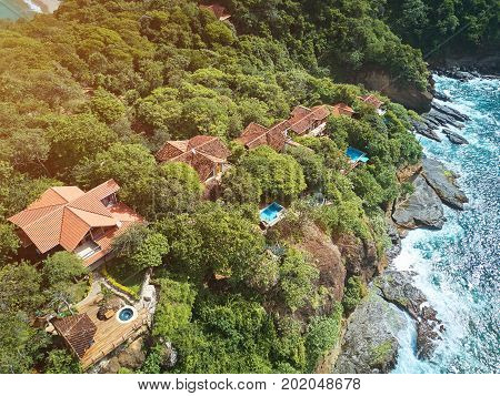 Villas and houses in cliff next to ocean aerial drone view