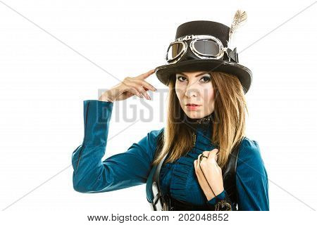 Young steampunk islolated girl on white touching fancy hat. Fantasy old fashion with stylish topper and goggle.