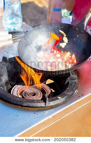 Tossing Vegetables In A Wok. Cook Prepares A Dish With Fresh Vegetables Outdoors.