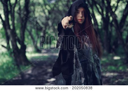 Foto of dark forest with witch in cloak and hood with outstretched hand