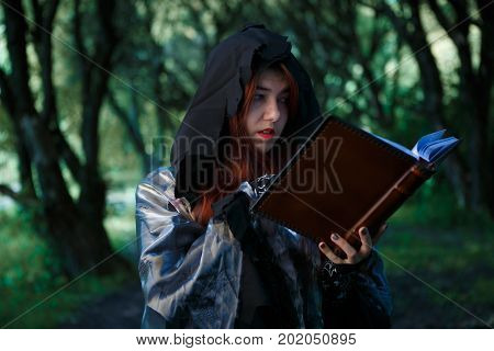 Photo of witch with spell book in dark forest