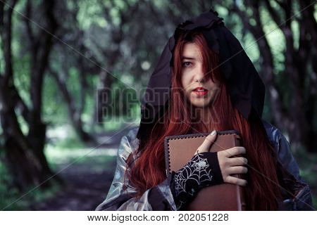 Portrait of witch with book of incantations in black cloak in forest