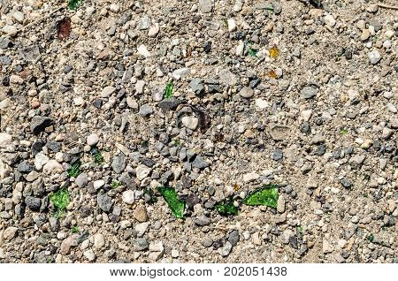 Background made of close-up photo of ground with crushed stone and pieces of green glass