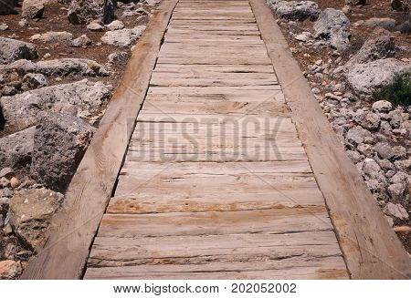 Part of wooden path on ground with stones