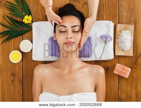 Face lifting massage in indian aroma spa wellness center to beautiful girl in cosmetology cabinet or beauty parlor.