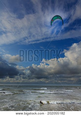 Lonely kite surfer against blue cloudy sky in summer, Palanga, Lithuania, Europe