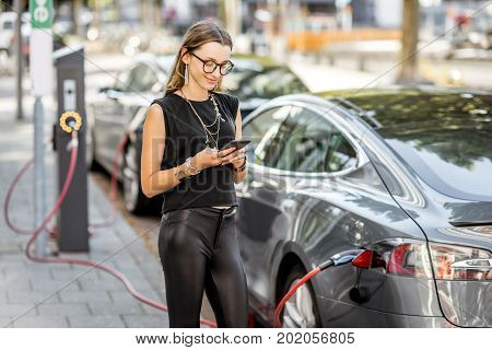 Young woman charging electric car standing with smart phone outdoors on the street in Rotterdam city