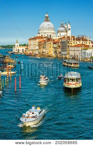 Venice, Italy - May 18, 2017: Water taxis with tourists are sailing along the Grand Canal in Venice. Motor boats are the main transport in Venice. Santa Maria della Salute church in the distance.