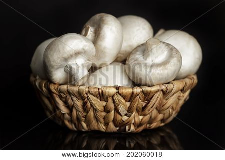 Mushrooms Champignons In A Wicker Basket On A Black Background