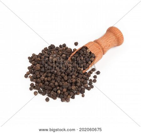 Wooden shovel with black peppercorn scattered from it.