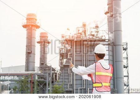 Asian man worker and engineer electrician work safety control at power plant energy industry people work Thailand. Engineer Conceptelectric engineer with drawings working in a power plant