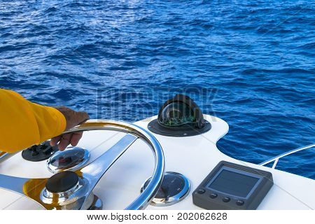 Hand of captain on steering wheel of fishing motor boat in the blue ocean durig fishery day