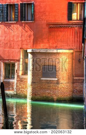 An empty canal in Venice with a sliver of sun light.