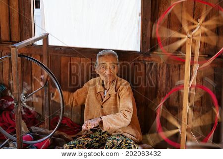Inle Lake Myanmar - January 04 2007: Old woman of Intha people working at home in village on Inle lake in Shan state spinning yarn by hand for traditional Burmese handmade textile.