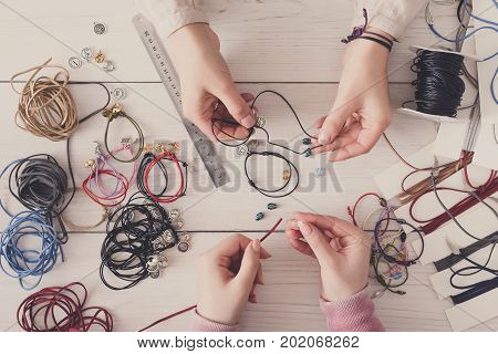 Handmade jewelry making, female hobby. Two women creating bracelets at home workshop, top view on workplace. Fashion, handicraft concept