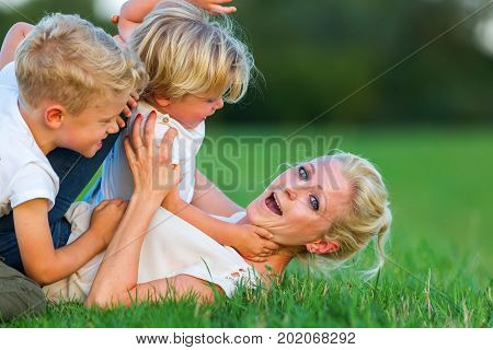 Woman Romps With Her Two Sons On The Grass