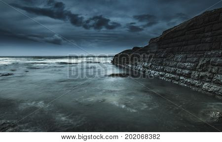Eerie Seascape at Twilight, Ocean and Wave Crashing Structure at Summer Evening Before Storm