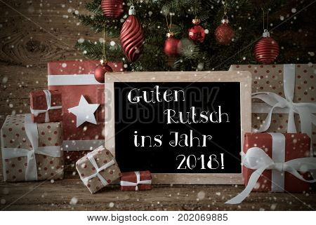 Nostalgic Card For Seasons Greetings. Christmas Tree With Balls And Snowflakes. Gifts In The Front Of Wooden Background. Chalkboard With German Text Guten Rutsch Ins Jahr 2018 Means Happy New Year
