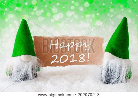 Christmas Greeting Card With Two Green Gnomes. Sparkling Bokeh And Natural Background With Snow. English Text Happy 2018