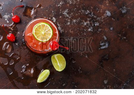 Red cocktail on brown background. Refreshing alcohol drink with tequila, citrus juice, lime and maraschino cherry on marbled table with melting ice, copy space, top view