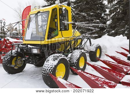 Yellow tractor seeder on winter snow, outdoor