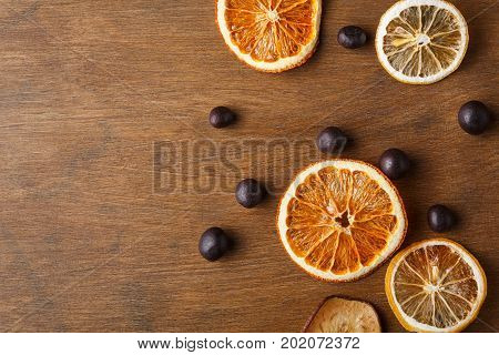 Dry orange, lemon, apple slices and small round chocolate sweets on wooden board. Candied citrus citrons top view with copy space. Cooking, confectionery or christmas background concept