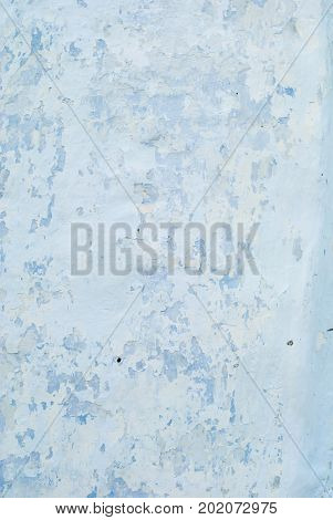 An old whitened white with a blue wall with cracks for a background or texture of pale color vertical.