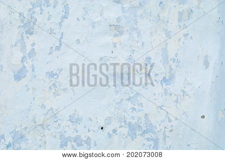 An old whitened white with a blue wall with cracks for a background or texture of pale color horizontal.