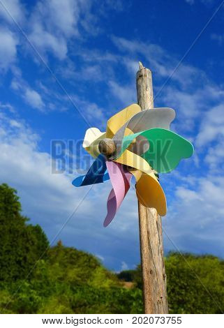 Close up macro detail of colorful pinwheel attached to the pole on blue sky background.