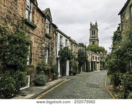 EDINBURGH SCOTLAND - 29 AUGUST 2017: The curve of a beautiful traditional cobbled street in Stockbridge area of Edinburgh