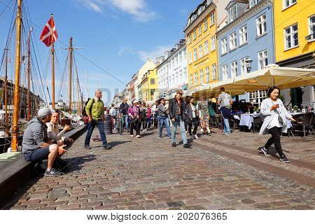 Copenhagen Denmark - August 24 2017: People valking the street in Nyhavn there restaurants with outdoor seating are located.