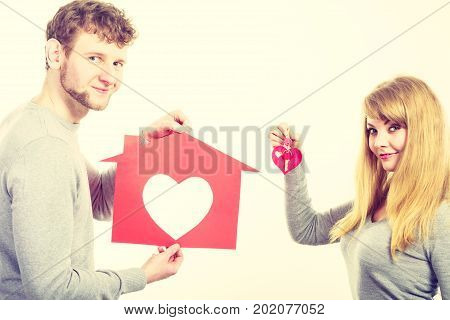 People fresh start real estate and love concept. Young enjoyable enamoured marriage holding red house with big heart and keys to their future.