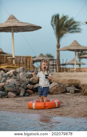 Baby care and childhood concept. Small kid laughing in orange life ring at beach. Happiness and expressive emotions. Safety on water on summer vacations. Boy child standing with hands up in life buoy.
