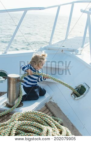 Yachting and sailing concept. Little child sitting and berthing rope on white boat. Travel and summer vacations. Baby care and childhood. Boy kid playing with rope on yacht.