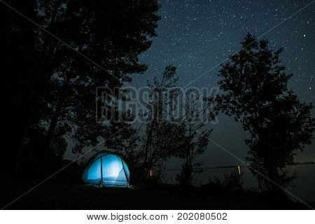 Blue tent set among trees on the coast of a river and night starry sky