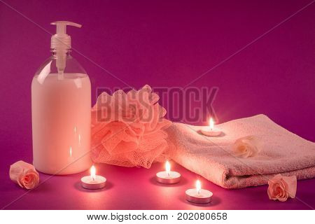 Shower gel bath sponge towel with some flowers and candles are on pink background. Shower bath wellness and spa.