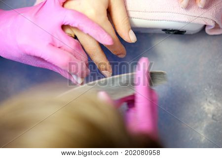 Manicurist polishing nails using nailfile in pink latex gauntlets